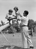 1950s Father Lifting Son and Daughter onto a Playground Seesaw Outdoor Papier Photo