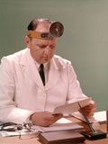 1960s Man Doctor Seated at Desk Reading Paperwork Photographic Print