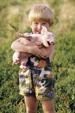 Smiling Blond 4 Year Old Boy Holding Squealing Baby Pig Photographic Print