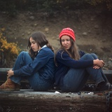 1970s Two Sad Serious Teenage Girls Sitting Back to Back Outside Photographic Print