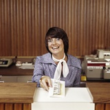1970s Smiling Woman Bank Teller Handing Cash over Counter Photographic Print