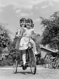 1940s Twin Girls Riding Outside on Tricycle Photographic Print