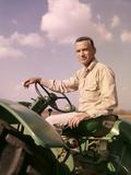 1960s Portrait Man Farmer Sitting on Green Tractor Smoking Cigarette Photographic Print