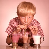 1950s-1960s Boy Drinking Three Milkshakes Through a Straw at Same Time Photographic Print