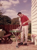 1960s Man Wearing Red Shirt Cooking Steak Outdoor on Backyard Grill Photographic Print