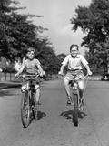 1930s-1940s Two Boys Riding Bikes on Tree Lined Street Photographic Print