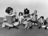 1930s Girl Pointng a Finger Reading to a Row of Dolls Toys Stuffed Animals Photographic Print