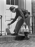 1940s Milkman Setting Glass Bottles of Milk and Cream in Front of Door Photographic Print