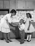 1960s Woman in Apron and Pumps Giving a Glass of Milk to Son and Daughter Photographic Print
