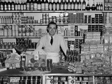 1940s Grocer Standing Behind Counter Filled with Various Food Products Photographic Print