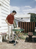 1960s Man Wearing Red Shirt Grilling Steak on Backyard Brick Patio Photographic Print
