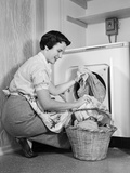1950s Woman Kneeling Removing Clothes Laundry from Automatic Dryer Stampa fotografica