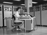 1960S Woman in Mainframe Computer Room Surrounded by Many Data Tape Drives Sitting at Desk Typing Photographic Print