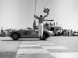 1960s Man Jumping Waving Checkered Flag as Winning Sports Car Crossing the Finish Line Photographic Print