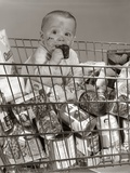 1960s Baby Sitting in Supermarket Cart Full of Cans Eating Candy Bar with a Messy Face Photographic Print