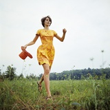 1970s Young Woman Wearing Colorful Print Dress Running in Field Carrying Red Straw Hat Photographic Print
