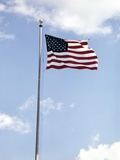 1960s American Flag on Pole Flying Against Blue Sky with Clouds Photographic Print