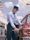 1950s-1960s Service Station Attendant with Gasoline Pump Hose Filling Gas Tank of Automobile Lámina fotográfica
