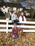 1960s Family with Dog at White Board Fence in Front of Colonial Style Suburban House Photographic Print