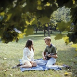 1960s-1970s Retro Smiling Couple Sitting on Blanket on Grass Park, Man Playing Acoustic Guitar Photographic Print