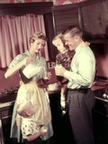 1950s Family in Kitchen Mother Pouring Milk from Pitcher for Dad and Kids Lámina fotográfica