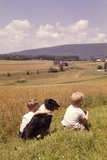 1960s Back of Two Boys with Black and White Dog Sitting Hillside Field Looking Down to Farm Photographic Print