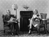 1940s Senior Couple Sitting in Living Room Reading Newspaper and Magazine Listening to Radio Photographic Print