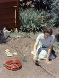 1950s Woman Kneeling in Garden Planting Seeds in Soil Photographic Print