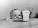 1950s Toddler Reaching Up to Table to Grab Milk Glass Photographic Print