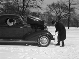 Woman Passenger Watching Man Motorist Try to Crank Start a Chevrolet Coupe Stalled in Snow Photographic Print