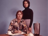 1970s Husband Wearing Loud Print Shirt Writing Family Budget and Wife Standing Behind Coffee Pot Photographic Print