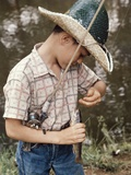 Boy Wearing Straw Hat Removing Hook from Mouth of Fish Outdoor Photographic Print