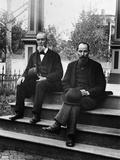 1890s-1900s Two Bearded Men in Suits Holding Bowler Hats Sitting on Stairs in Front of House Fotografiskt tryck