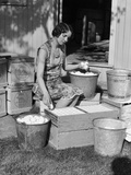 1930s Farm Wife Sitting Outside of Hen House Doorway Putting Eggs from Pails into Shipping Crates Photographie
