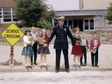 1960s Police Officer Holding Back Elementary School Children Waiting at Curb to Cross Street Photographic Print