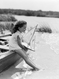 1930s Young Girl at Seashore Holding Sailboat Toy Sitting on Edge of Rowboat Feet in Water Reproduction photographique