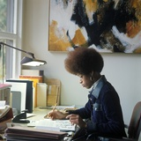 1960s-1970s African-American Woman Sit at Desk Write on Papers Photographic Print