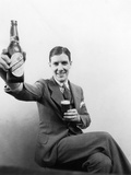 1920s-1930s Man Holding Up Huge Distorted Beer Bottle and a Regular Size Glass of Beer Photographic Print