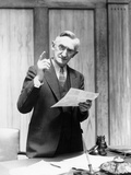 1930s Elderly Man in Office Standing Behind Desk Gesturing with Raised Finger Photographic Print