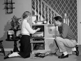 1950s Teenage Couple Playing Hi-Fi Records on Console Phonograph in Living Room Photographic Print