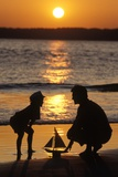 1990s Anonymous Father and Son Playing with Toy Boat at the Beach Silhouetted Against Setting Sun Lámina fotográfica