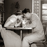 1950s-1960s Laughing Teenage Boy and Girl Sharing Drink Together with Two Straws in Soda Shop Photographic Print