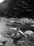 1920s Man in Stream Wearing Waders with Fish on Line Trying to Catch it in Net Impressão fotográfica