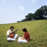 1970s African-American Couple Man Woman Sitting on Grassy Hill Man Playing Acoustic Guitar Photographic Print