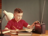 1960s Red Hair Boy Sitting at Deslistening to Portable Radio While Studying Homework Photographic Print