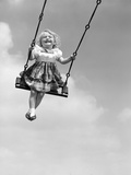 1950s Laughing Little Girl Swinging High on Outdoor Swing Photographie