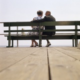 1970s Back View of Senior Couple Sitting on Boardwalk Bench Overlooking Ocean Beach Photographic Print