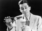 1930s Man Pouring Beer from Bottle into Glass Look of Anticipation Wearing Suit Tie Sweater Photographic Print