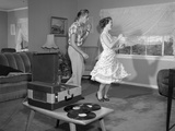1950s Laughing Teenage Couple Dancing to the Phonograph Playing 78 Rpm Records in Living Room Photographic Print