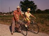 1970s Senior Elderly Retired Couple Riding Bikes Wearing Straw Hats Hawaiian Print Shirts Photographic Print